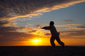 Chinese elderly woman performing taichi outdoor morning by the beach under sunset sunrise silhouette Stock Photography