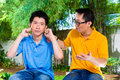 Chinese father gives his son some advice asian talking to but he will not listening holding ears with hands refusing the good Stock Image