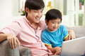 Chinese Father And Son Using Laptop Stock Image