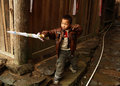 Chinese five year old boy playing with a plastic sword in the village street editorial images from of minority xiaozhai province Royalty Free Stock Photo