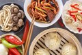 stock image of  Chinese food on a gray wooden table. Traditional steam dumplings, noodles, vegetables, seafood.