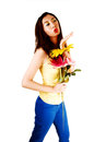 Chinese girl blowing kiss a tall young woman standing for white background in blue pants and yellow top a and holding some flowers Royalty Free Stock Photography