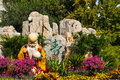 Chinese god of longevity the statue is smiling standing in the park with colorful flowers and plants Stock Photography