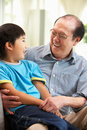 Chinese Grandfather And Grandson Relaxing At Home Royalty Free Stock Photos