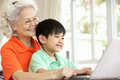 Chinese Grandmother And Grandson Using Laptop Stock Photos