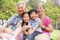 Chinese Grandparents Sitting With Grandchildren Stock Image