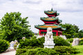 Chinese guardian lion and japanese pagoda zen garden in front of a with elevated tiled or thatched roof Stock Image
