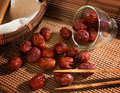 Chinese jujube dried red date or traditional herbal medicine spill on bamboo mat Stock Photo