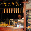 Chinese man at grilled meat food stand