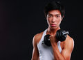 Chinese man working out with dumbbell on black background Royalty Free Stock Photos