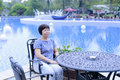 Chinese middle-aged woman sitting on a chair beside the pool Royalty Free Stock Photo
