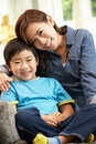 Chinese Mother And Son Sitting On Sofa Royalty Free Stock Image
