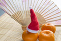 Chinese New year tangerines hat and hand fan on bamboo Mat Royalty Free Stock Photo