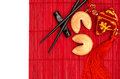 Chinese new years lucky charm fortune cookies and chopsticks asian style table place setting with on red bamboo mat Stock Image