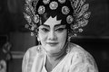 A Chinese opera actress painting mask on her face before the performance at backstage at major shrine in Bangkok's chinatown on Oc Royalty Free Stock Photo