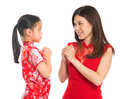 Chinese parent and child greeting to each other happy new year in traditional cheongsam isolated on white Royalty Free Stock Photography