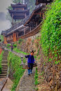 Chinese peasant is gravity on the background of wooden pagoda xijiang village leishan county guizhou china april work rural in Royalty Free Stock Photo