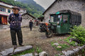 Chinese peasants in village street, next to three-wheeled green car. Royalty Free Stock Photo