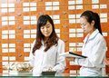 Chinese pharmacy worker in china drugstore two cheerful pharmacist chemist women standing Stock Images
