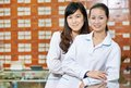 Chinese pharmacy worker in china drugstore two cheerful pharmacist chemist women standing Stock Photos