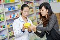 Chinese pharmacy worker in china drugstore two cheerful pharmacist chemist women standing Stock Photography