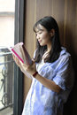 Chinese Portrait of young beautiful woman reads Book In Bookstore