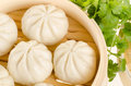 Chinese steamed buns in bamboo steamer basket with cilantro on w Royalty Free Stock Photo