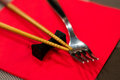 Chinese sticks and a fork on a red serviette Royalty Free Stock Photography