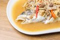 Chinese style marinated steamed fish with onion and ginger in plate Stock Images