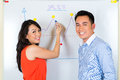 Chinese team in a advertising agency asian creative two colleagues showing the development of sales with diagram on whiteboard Stock Image