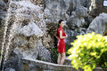 Chinese woman in cheongsam by a fountain in Mudu ancient town