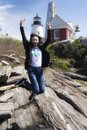 Chinese woman jumping pemaquid lighthouse background Royalty Free Stock Photo
