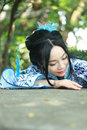 Chinese woman in traditional Blue and white Hanfu dress Climb over the stone table