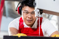 Chinese worker on saw in industrial factory Royalty Free Stock Photo