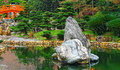 Chinese zen garden with red bridge and rocks Royalty Free Stock Photo