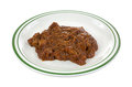 Chipped barbecue pork in gravy on plate a large serving of a green striped Royalty Free Stock Image