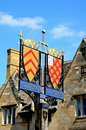 Chipping campden town sign colourful wrought iron with a sword on a wooden post along the high street the cotswolds Stock Image