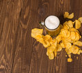 Chips and frothy beer the with crunchy on the table Royalty Free Stock Images