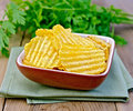 Chips grooved in bowl on board a clay a napkin parsley a wooden boards background Stock Photography