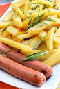 Chips and sausages rustic big potatoes slice fried with rosemary aroma herbs Stock Photos