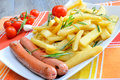 Chips and sausages rustic big potatoes slice fried with rosemary aroma herbs grilled sausage Stock Image