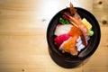 Chirashi sushi, Japanese food rice bowl with raw salmon sashimi, mixed seafood, top view, darken edge Royalty Free Stock Photo