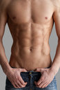 Chiseled chest and abs cropped image of muscular man standing isolated on grey background Royalty Free Stock Photo