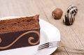 Chocolade cake on a white plate with tree chocolades Royalty Free Stock Photography