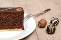 Chocolade torte on a white plate with three chocolates Royalty Free Stock Image