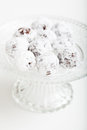Chocolate balls closeup of sprinkled with icing sugar on glass serving tray on light surface Stock Photo
