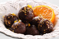 Chocolate balls and orange on white plate Royalty Free Stock Images
