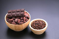 Chocolate bar and dried cocoa seed, cocoa nibs in wooden bowl on