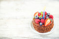 Chocolate birthday cake with candles, raspberries, blueberries a