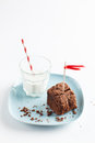 Chocolate brownie on plate served with milk slice of delicious homemade decorated red ribbon flag pale blue glass of Stock Photography